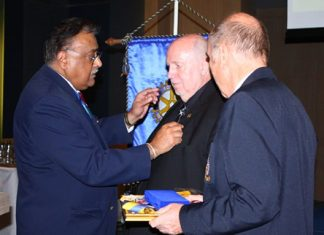 (L to R) Rotary District 3340 Past Gov. Peter Malhotra (left) pins the honorary Rotary badge on Reiner Calmund's jacket, as Club President Dr. Otmar Deter looks on.