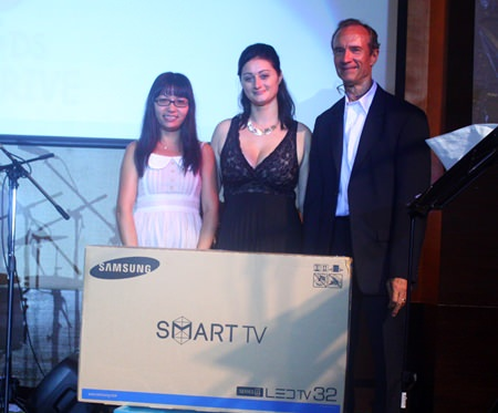 "(L to R) Ja was the lucky winner of the Samsung 32"" flat screen TV lucky draw prize, presented here by Deborah Philbrook and Woody Underwood."