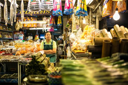 A vendor and her array of local snacks at Nong Mon market.