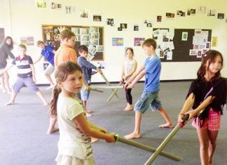 Campers practicing fantasy sword role playing.