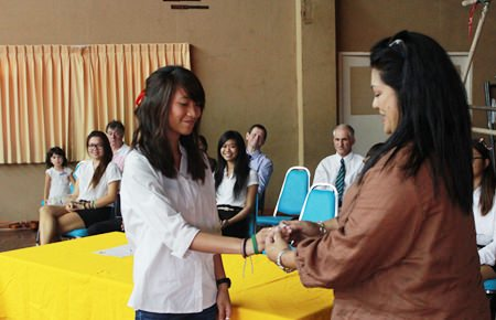 Humanities Prefect Trisha gets a special white GIS wristband from her mother.