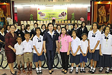 Red Cross Vice-President Sasithorn Preechawit leads members of the Chonburi Red Cross in handing out a million baht in scholarships and providing free bicycles.