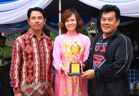 Siran Nimihut (right), GM of Siam Bayshore Resort and Spa, accepts the winning trophy for his team's float dedicated to Thailand joining the ASEAN Economic Community in 2015, from Bundarik Kusolvitya (center), president of THA Eastern region, and Mayor Itthiphol Kunplome.