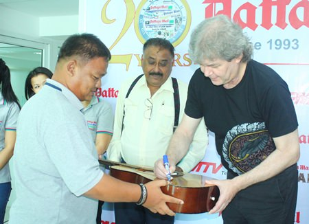 "Hucky autographs a guitar for head graphics man, Thanawat ""King"" Suansuk."