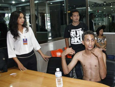 Bunjan Honphukiew (seated, shirtless) tries to explain to police what might have happened to him.