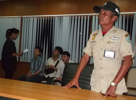"San Nongyai (standing) and his drunken ""gang"" (seated, background) have been charged with weapons, drugs and other offenses."