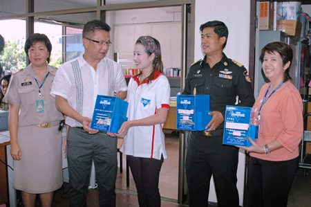 Deputy Mayor Wutisak Rermkitkarn (2nd left) receives the donations from Praichit Jetpai (center), President of the YWCA Bangkok- Pattaya Chapter as other important officials look on.