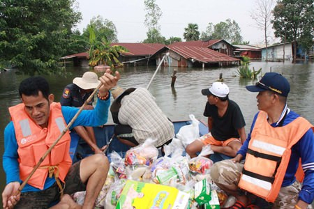 Relief workers paddle to inundated homes, bringing what relief supplies they can.
