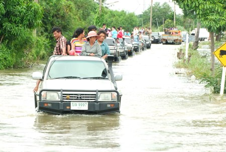 The governor and his entourage make their way into flooded Phanat Nikhom to hand out relief supplies.