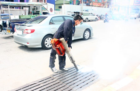 Officials from Pattaya's Public Health Department spray mosquito pesticide into the drains on Pattaya 2nd Road.