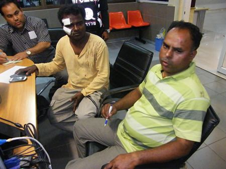 Karthikeyan Krishnan (center) and Kadher Basha (right) file a report with police about their being kidnapped and robbed.