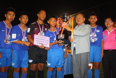 Nongpure municipal president Mai Chaiyanit (center-right) presents the champions trophy to the Chonburi FC under-13 team.
