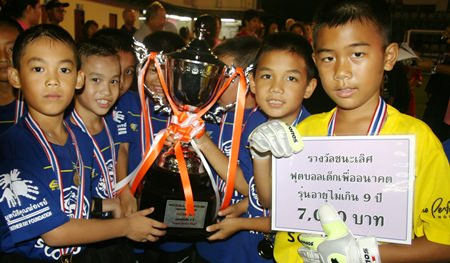 The under-9 team from Darasamuth School show off their winners' trophy, medals and cash prize.
