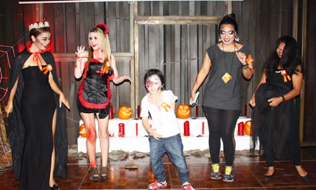 Contestants in the Zulu Bar's scary costume contest, won by the youngster in the middle, perform their scariest dance moves for the judges.