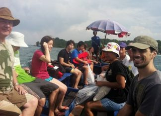 Volunteers from Rotary, Mahidol University and students from Argentina return to the boat after cleaning.
