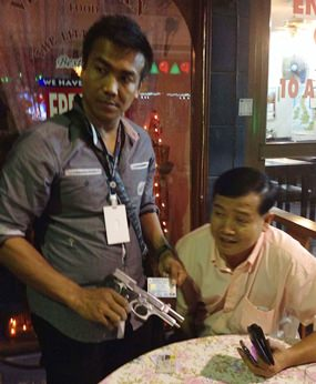 Police take the 9mm handgun and ID from Yuthana Khanthong during his arrest.