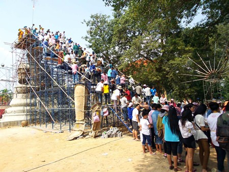 People form a bucket brigade to bring cement and precious items to be put on top of the new Buddha statue in Rayong.