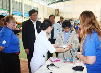 One Sight Clinic Manager Janet Duke (left) explains the Give the Gift of Sight project to Chonburi POA President Wittaya Kunplome (next).