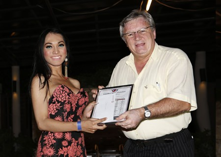 Father Giovanni (right) of the Camillian Trust is presented a check from Miss Indonesia.