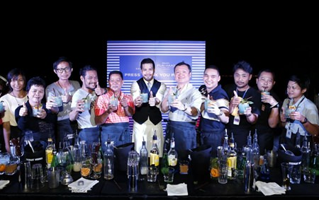 Sansiri executive Uthai Uthaisangsuk (5th right) and Niks Anuman-Rajadhon (center) pose for a photo with cocktail mixing members of the media at the exclusive party held at Baan Plai Haad on Nov. 22.