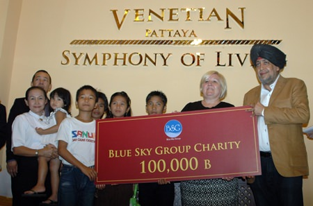 Surjeet Sing Chawala (right) presents a cheque for 100,000 THB to Tracy Cosgrove (2nd right) and the children of the Sanuk Day Care Center.