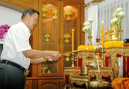 Gen. Kanit Permsub lights incense and candles to pay respects to Lord Buddha.