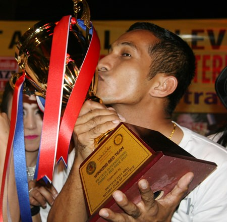 The captain of the winning team kisses the winners trophy.