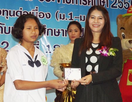 Suphatra Yenkasem, president of the Big C Foundation, presents a scholarship to one of the students.