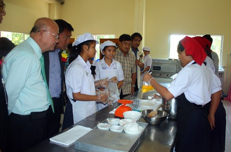Deputy Mayor Wattana Chantanawaranon (left) looks on as students learn how to bake in the school's bakery-training facility.
