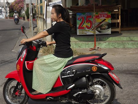 A woman rides her motorbike without a helmet on Central Pattaya Road.