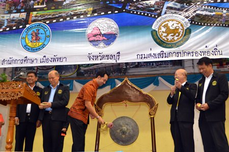 Mayor Itthiphol Kunplome strikes the gong to begin the anniversary party, as other school and city officials look on.