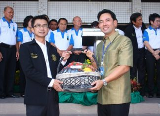 Pattaya City Manager Pakorn Sukonthachart (left), representing Pattaya officials and employees, gives a Happy New Year gift basket to Mayor Itthiphol Kunplome (right).