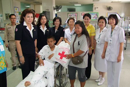 Chonburi Red Cross President Busarawadee Ekachai (left) presents cash and supplies to young hero, Sumet Kulprasart and his mother.