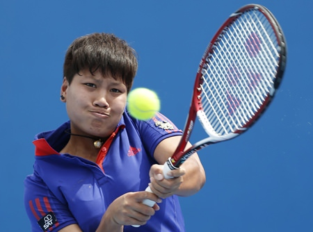 Luksika Kumkhum of Thailand makes a backhand return to Mona Barthel of Germany during their second round match at the Australian Open tennis championship, Wednesday, Jan. 15. (AP Photo/Shuji Kajiyama)