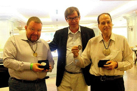 I.A.P.N. member Vasilijs Mihailovs (left) and Ronachai Krisadaolarn (right) stand with Thai coinage expert Jan Olav Aamlid (center) at the award ceremony in Bangkok.  Mihailovs and Krisadaolarn are displaying their I.A.P.N. book prize medals.