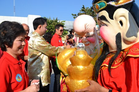 "Mayor Itthiphol Kunplome distributes ""ang-pao"" money envelopes to the Lao Si performers."