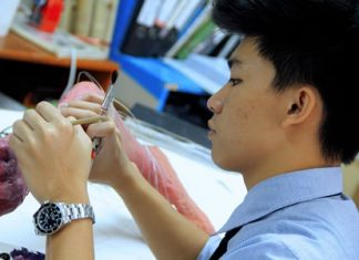 IB Student applies wire to his sculpture of two conjoined limbs, 'Be-reached'.