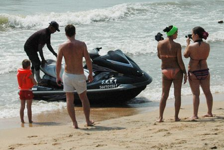 A young Russian tries to negotiate the price for alleged damage to the jet ski while his girlfriend takes photos.