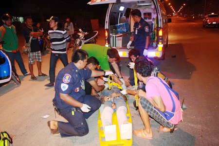 Rescue workers tend to the victim in the middle of Sukhumvit Highway.