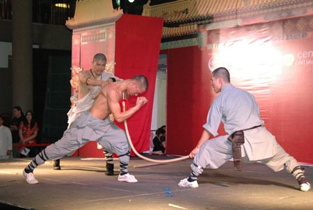 A Shaolin member uses his neck to push against a sharp spear while another Shaolin member hits his back with a wooden stick.
