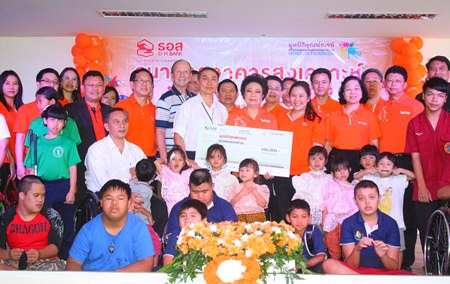 Angkhana Pilanowat Chimanas (center right), MD of the Government Housing Bank, presents a 100,000 baht donation to Father Pattarapong Srivorakul (center left), president of the Father Ray Foundation, to add to the vocational training building fund.