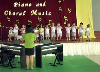A group of young students dance and sing 'Music is fun'.