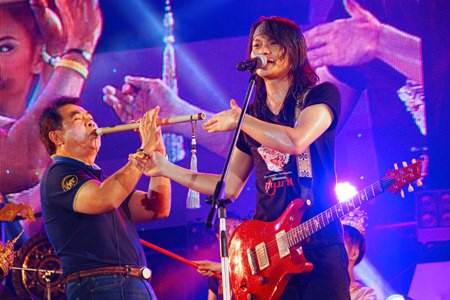 Thanit Sriklindee (left) showing off his flute skills as a special guest of Thanit Sriklindee surprising his fans at the Pattaya Music Festival on the final day.