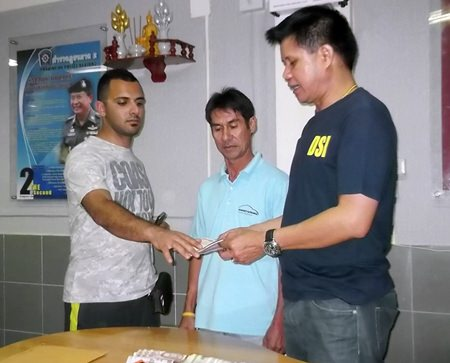 (L to R) Ramin Rajaeetabar receives his money and wallet back from taxi driver Wichian Phonkhong, overseen by Pattaya Police Superintendent Col. Supachai Puikaewkam.
