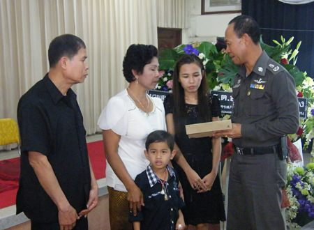 Pol. Maj. Gen. Khatcha Thatsart (right) presents the widow, her son and the deceased's parents with official compensation for the policeman's death.