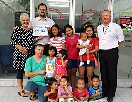 Eva Johnson (left) and Earl Brown (right) present a cheque for 50,000 baht to the children and organizers of the Take Care Kids charity.