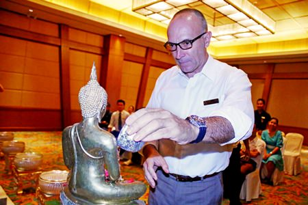 Robert John Lohrmann, General Manager of Centara Grand Mirage Beach Resort Pattaya, pours water on the hotel's Lord Buddha image.