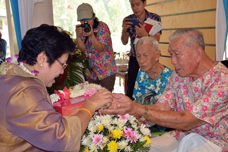 Yani Lerdkrai pours lustral water into the palms of respected elders.