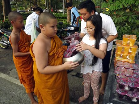 A father leads his daughter to offer alms.