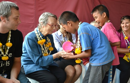 Children from Fountain of Life gently pour water on Sister Joan Gormley's hands, asking for blessing and expressing their gratitude.